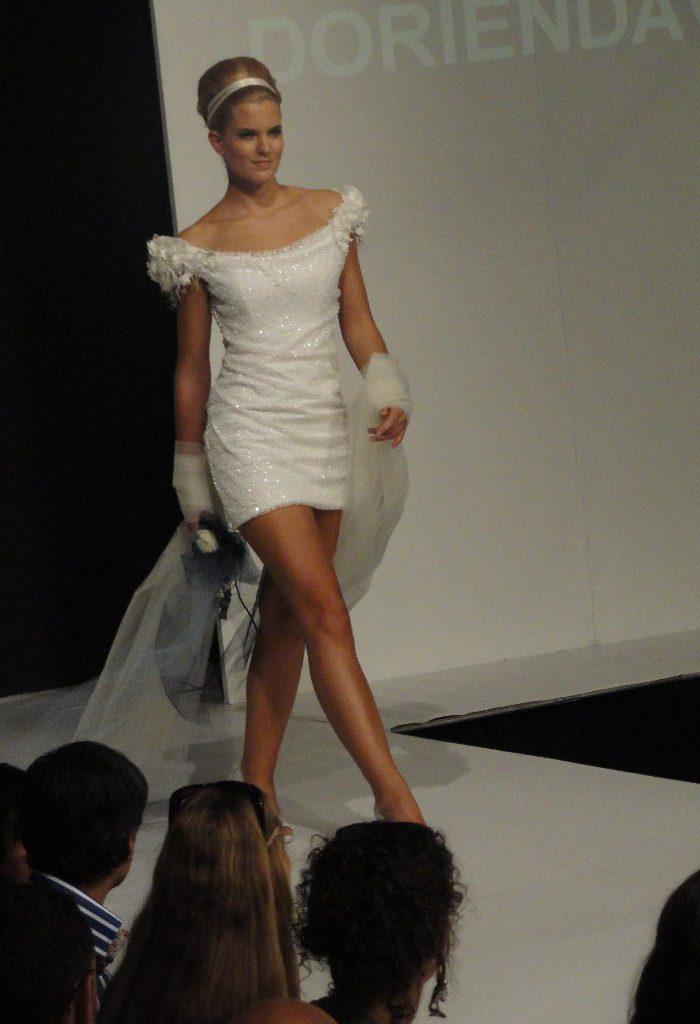 Kort bruidsjurkje van pailletten-stof, model Gisela in modeshow